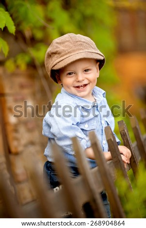 portrait of little smiling boy in the blue shirt and brown cap is standing near the wooden fence in the nature - stock photo