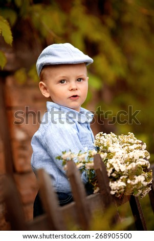 portrait of little smiling boy in the blue shirt and  cap is standing near the wooden fence in the garden with white flowers - stock photo