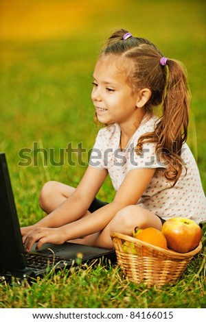 Portrait of little smiling pretty girl wearing t-shirt and shorts working with laptop at summer green park.