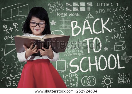 Portrait of little student standing in front of blackboard while reading a book with a text of back to school - stock photo