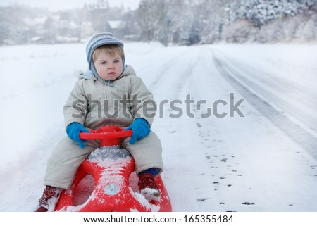Portrait of Little toddler boy sitting on sledge in winter clothes with falling snow - stock photo