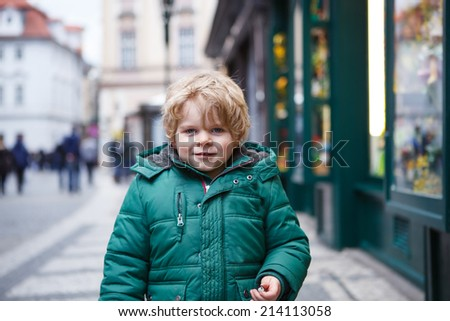 Portrait of little toddler boy walking through the city on cold winter day. - stock photo
