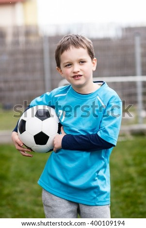 Portrait of little 7 years boy - footballer with football ball. Child playing football in garden. Wears a blue t-shirt, black and blue shoes and grey sweatpants.  - stock photo