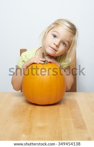 Portrait of little young child blond girl sitting at a table embracing pumpkin - stock photo