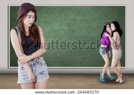 Portrait of lonely teenage girl standing in the class while mocked by her friends - stock photo