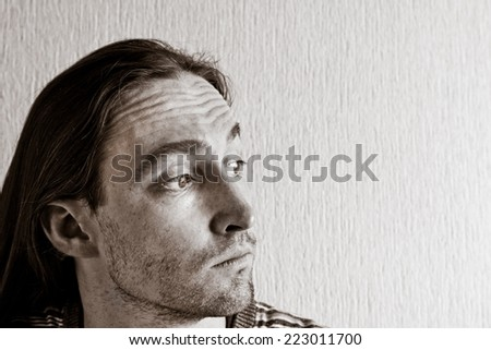 Portrait of long hair handsome thinking man. Black and white image