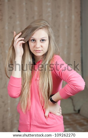 portrait of long-haired blonde girl in home interior - stock photo