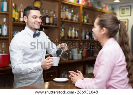 Portrait of long-haired young girl flirting with smiling handsome barman at counter