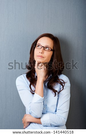 Portrait of looking up woman with hands on her chin - stock photo
