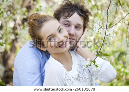 Portrait of love couple embracing in spring flowers - stock photo