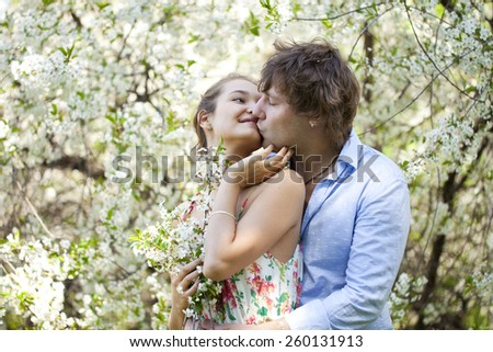 Portrait of love couple embracing in spring flowers