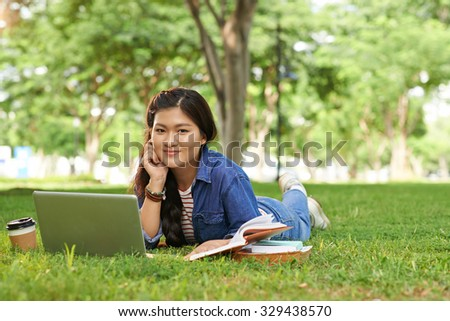 Portrait of lovely Asian college girl doing homework on campus