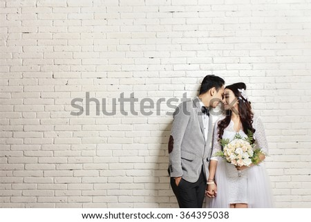 portrait of lovely asian newlywed couple with copy space on white wall background - stock photo