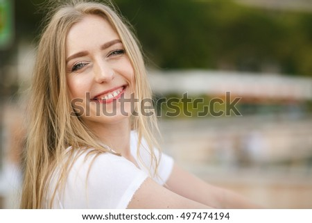 Portrait of lovely blonde with straight hair and charming smile