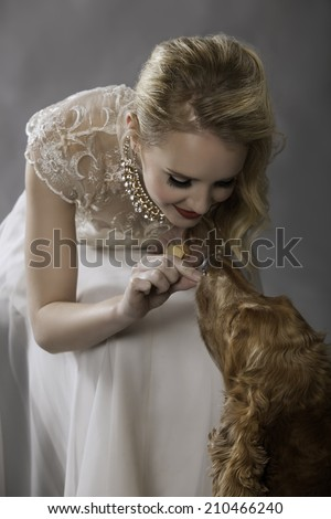 Portrait of lovely blonde woman in vintage dress feeding her cute golden Spaniel dog a treat while smiling affectionately at her pet - stock photo