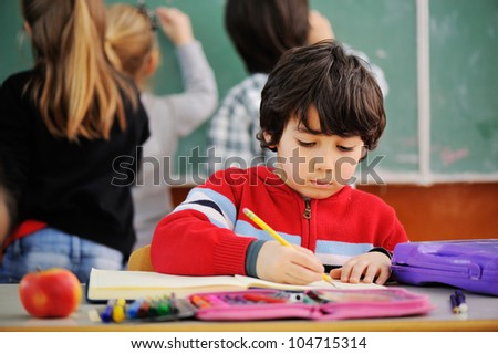 Portrait of lovely boy drawing in copybook at school - stock photo