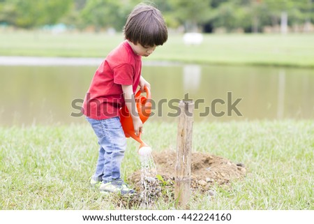 Portrait of Lovely Boy Watering Plants Outdoors - stock photo