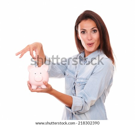 Portrait of lovely charming woman on blue blouse with her piggybank smiling at you on isolated studio