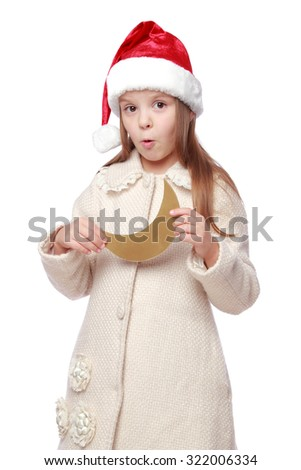 Portrait of lovely cheerful little girl with healthy long hair in Santa hat holding a moon isolated on white/Studio image of a cute child in a Santa hat with a golden moon - stock photo