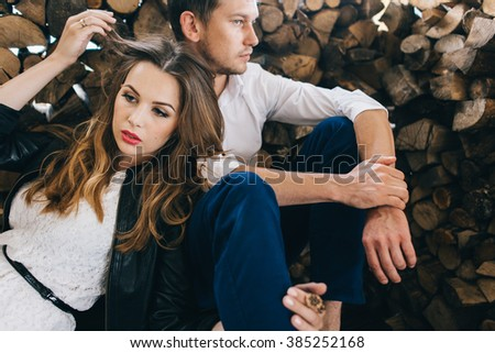 portrait of lovely couple. Beautiful woman in leather jacket and blue hat near the man.beauty girl and boy together are standing on the wooden outdoor background