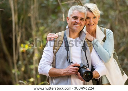 portrait of lovely couple hiking in forest - stock photo