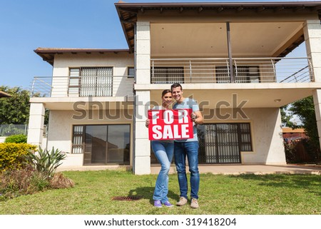 portrait of lovely couple holding for sale sign in front of house