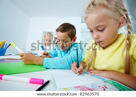 Portrait of lovely girl and her classmates drawing with highlighters at lesson