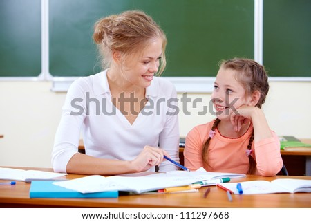 Portrait of lovely girl and her teacher drawing at lesson - stock photo