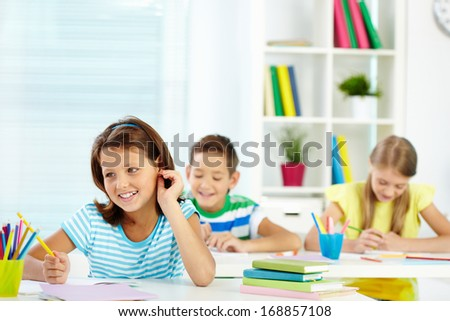 Portrait of lovely girl and her two schoolmates on background sitting at lesson - stock photo