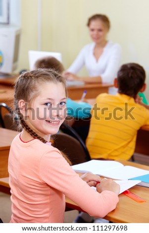 Portrait of lovely girl at workplace with schoolboys and teacher on background - stock photo
