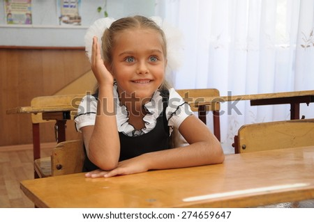 Portrait of lovely girl in classroom. schoolgirl at the desk, little schoolgirl sitting at an empty desk, class 1 exhaust, the girl raised her hand in class