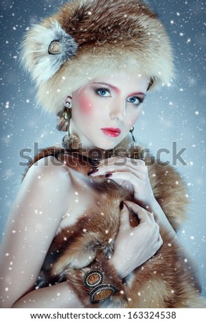 portrait of lovely girl in fur clothes with falling snowflakes against blue background - stock photo