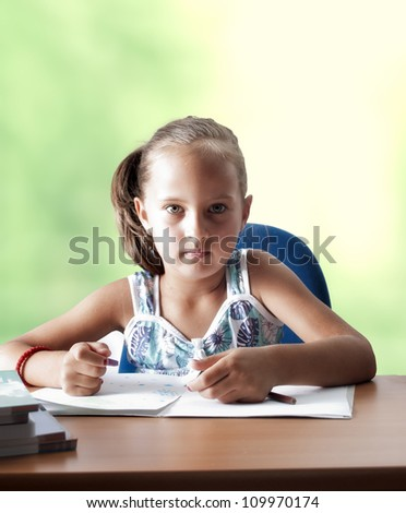 Portrait of lovely girl looking at camera while drawing,back to school concept