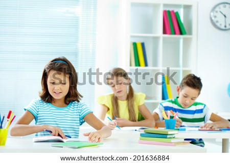 Portrait of lovely girl sitting at workplace with schoolmates drawing on background