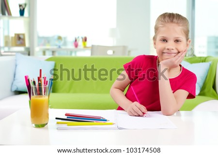 Portrait of lovely girl with colorful pencils looking at camera