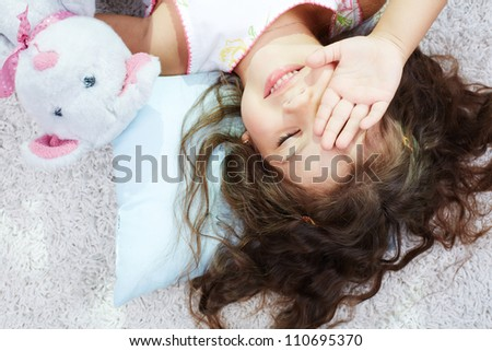Portrait of lovely girl with teddybear rubbing her eyes after sleep - stock photo