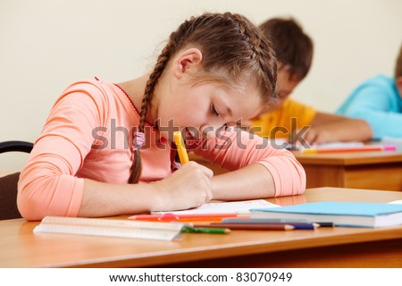 Portrait of lovely girl writing in copybook with schoolboys on background