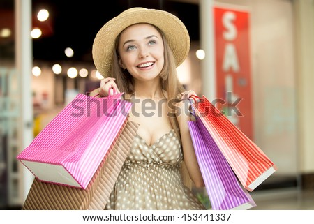 Portrait of lovely happy fashion woman wearing hat and dress standing in shopping centre smiling looking sideways and holding colorful shopping bags in both hands. Red sale sign on background