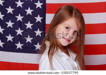 Portrait of lovely happy young girl with long hair and a beautiful smile is on the background of the flag of America