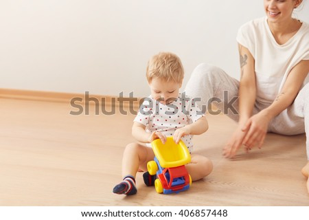 Portrait of lovely infant playing with toy truck sitting on the floor at home with interested look while his young mother sitting behind and watching him enjoy the game. Pastel colors. Selective focus - stock photo