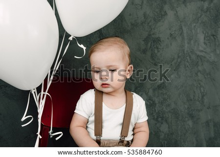 Portrait of lovely little boy happy smiling celebrating 1 year birthday. One year old european boy sitting on floor in studio