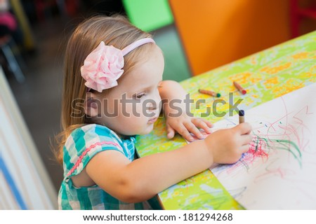 Portrait of lovely little girl drawing with color crayons. Selective focus - stock photo