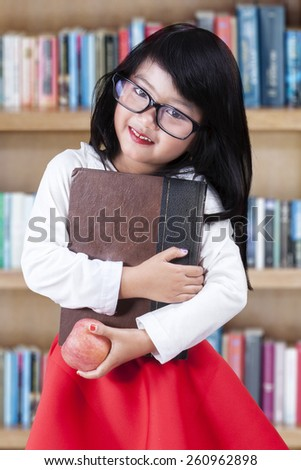 Portrait of lovely little girl standing in the library while holding a book and apple - stock photo