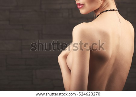 portrait of lovely naked woman covering her breast against beige background