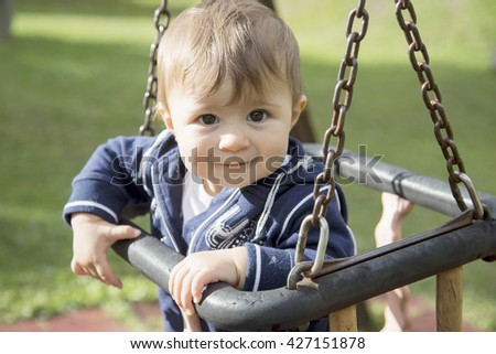 Portrait of lovely one year old baby girl sitting on swings at playground