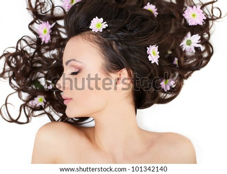 Portrait of lovely pretty beautiful brunette girl lying with bright colorful flowers in her hair bright makeup isolated on white