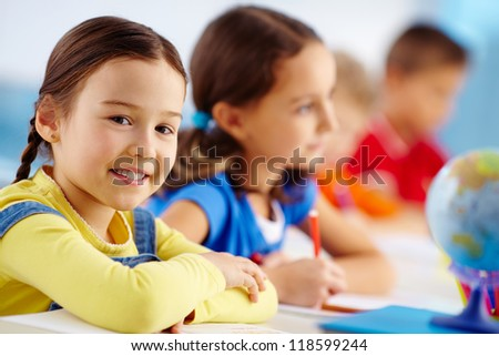 Portrait of lovely schoolgirl at workplace looking at camera with her classmates behind - stock photo