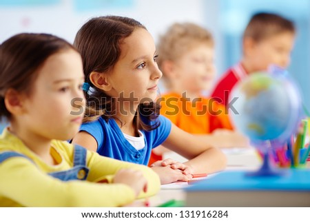 Portrait of lovely schoolgirl at workplace looking straight among her classmates