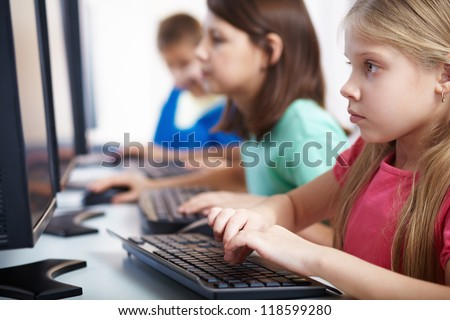 Portrait of lovely schoolgirl looking at computer monitor while typing - stock photo