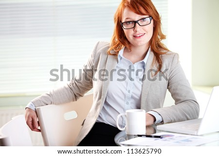 Portrait of lovely secretary looking at camera at workplace